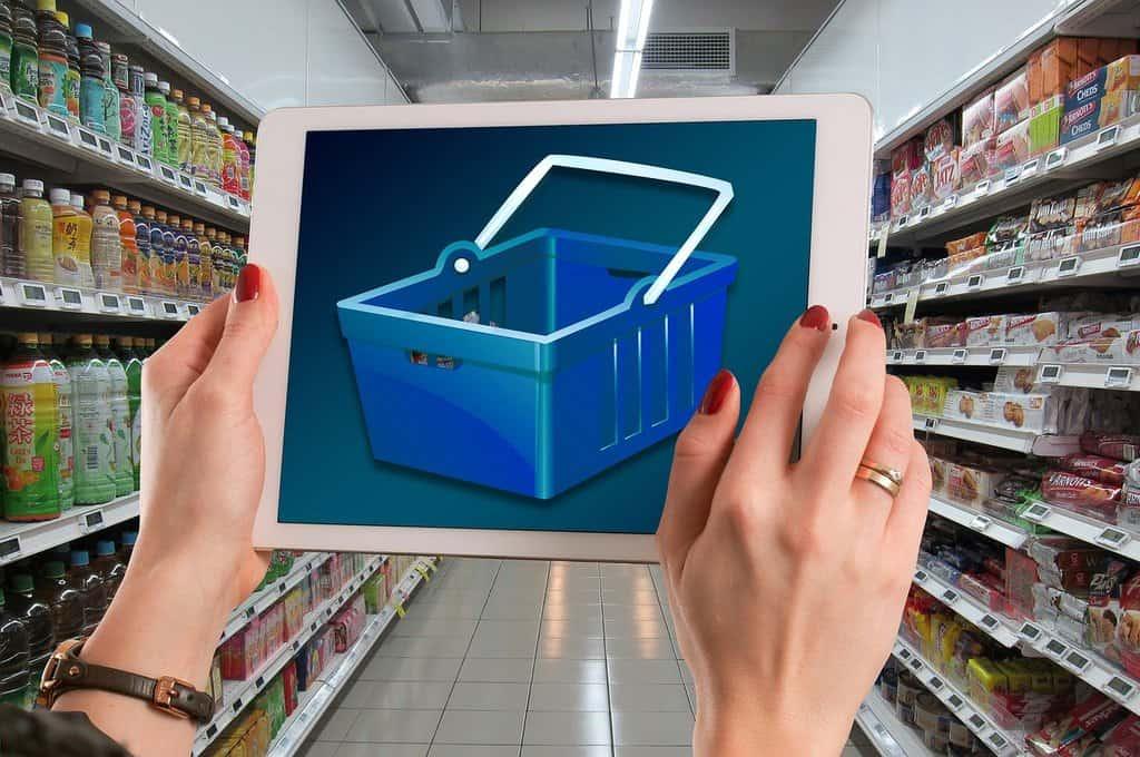 tablet ze zdjęciem koszyka zakupowego trzymany w dłoniach na tle półek sklepowych