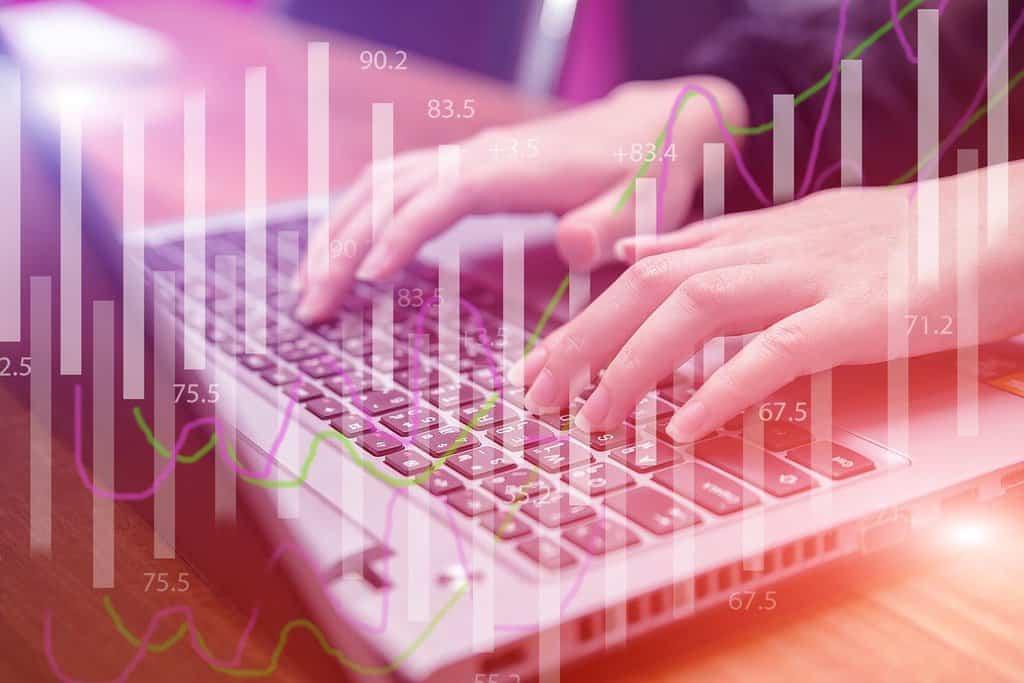 wykres słupkowy na tle laptopa z piszącymi na nim dłońmi
