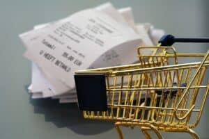 złoty wózek sklepowy na tle papierowych paragonów ze sklepu