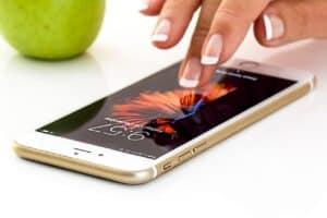 smartfon leżący nastole zkobiecą dłonią
