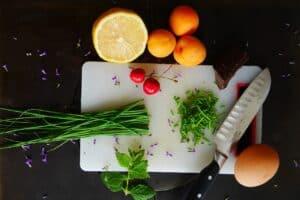 warzywa i nóż położone na desce do krojenia