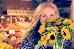 kobieta ze słonecznikami stojąca w sklepie
