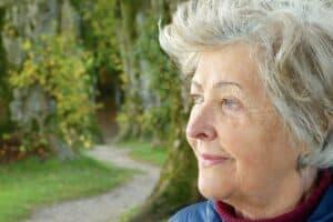 starsza kobieta na tle parkowej uliczki