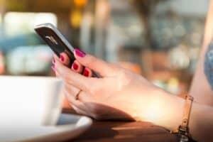 telefon trzymany przez kobiece dłonie nad filiżanką