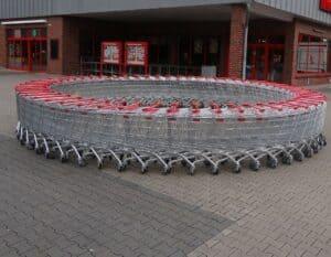 wózki sklepowe ustawione w kole przed sklepem spożywczym