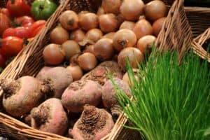cebula, buraki, pomidory i szczypior ułożone w sklepochych skrzyniach