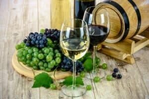 dwa kieliszki z białym i czerwonym winem na tle kiści winogron i beczułki z winem