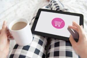 kobieta w piżamie siedząca na łóżku z kawą i tabletem